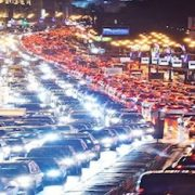 cars in dark traffic jam at night with lights on