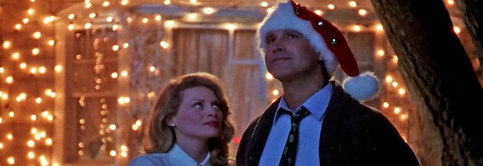 the Griswolds looking at the sky in front of a house with Christmas lights